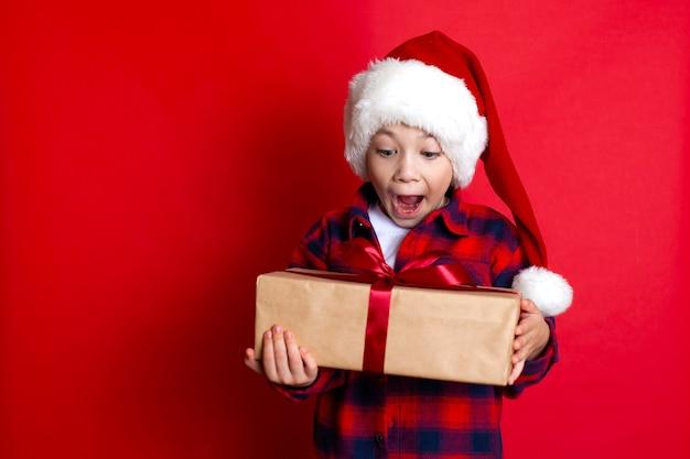 Buone vacanze e buon natale. ritratto di un ragazzo sorpreso e divertente in un berretto con regali in mano su uno sfondo rosso. un posto per il testo. foto di alta qualità