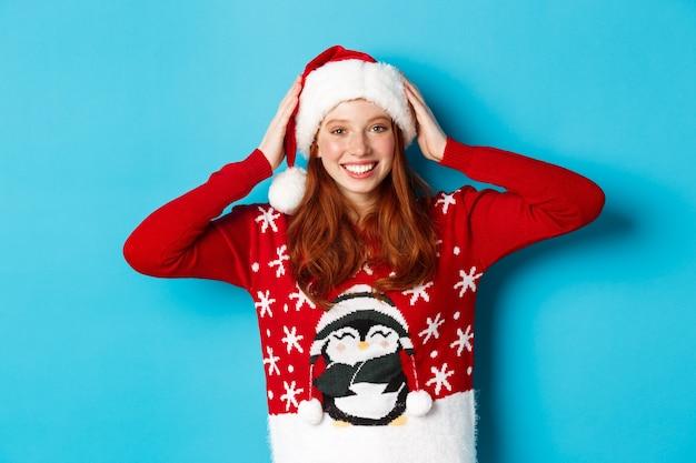 Buone vacanze e concetto di natale. bella ragazza dai capelli rossi con un maglione natalizio, indossa un cappello da babbo natale e sorride, festeggia il nuovo anno, sfondo blu