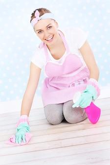 Una governante felice in stile retrò che pulisce un pavimento in legno su carta da parati punteggiata bianca e blu