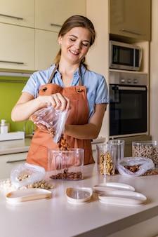 Felice casalinga in grembiule che versa noci secche fresche nell'organizzazione di stoccaggio del barattolo di vetro in cucina