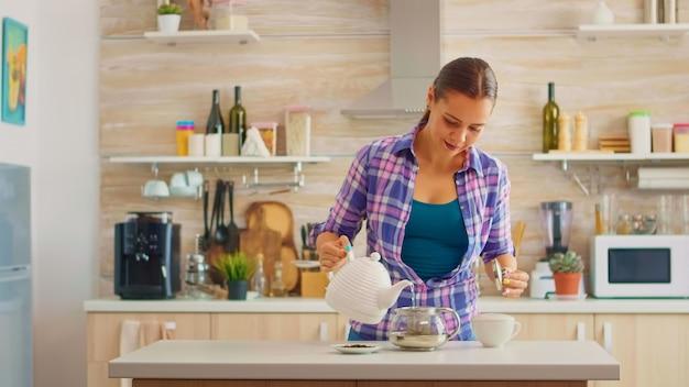 Felice casalinga che versa acqua calda nella teiera per preparare il tè verde per la colazione del mattino. cucina moderna seduta vicino al tavolo, con in mano il bollitore, in attesa di una sana tisana infusa.