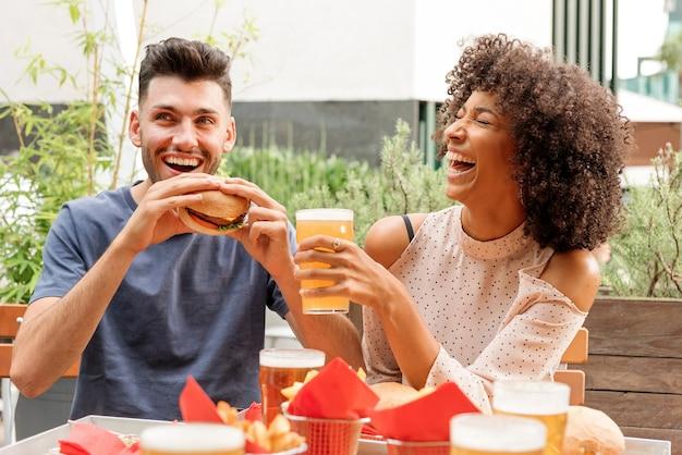 Felice coppia multiculturale affamata che si gode hamburger e birre fredde in un ristorante o pub all'aperto ridendo felicemente di una buona barzelletta