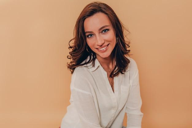 Felice donna incredibile con i capelli scuri ricci e sorridente sul muro beige che indossa una camicia bianca