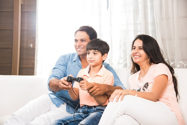 Felice famiglia asiatica indiana che gioca a un videogioco a casa con un joystick o un controller