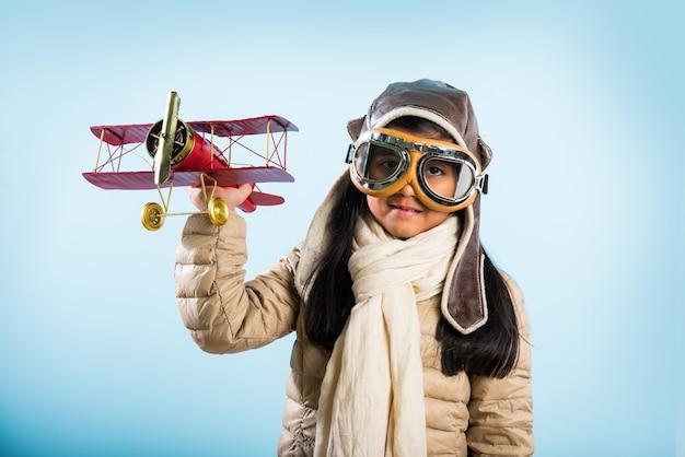 Felice ragazza indiana o asiatica che vola su un aeroplano di metallo giocattolo o saluta sullo sfondo della bandiera indiana - bambino e vola per il paese