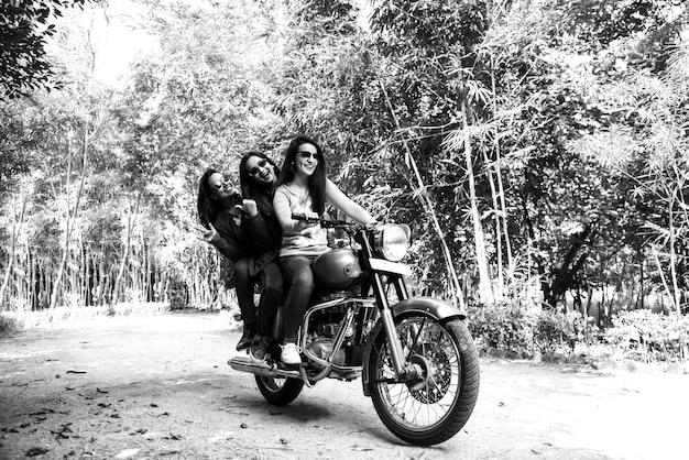 Felice asiatica indiana felice giovane donna o amiche in sella a moto o moto sulla strada forestale