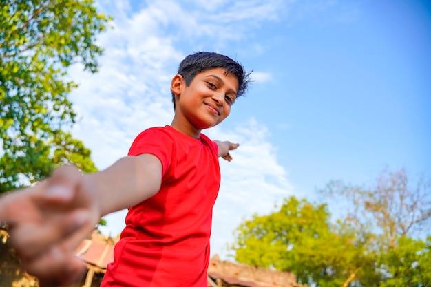 Bambino indiano felice che gioca alla terra