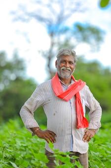 Felice contadino indiano al campo di cotone verde