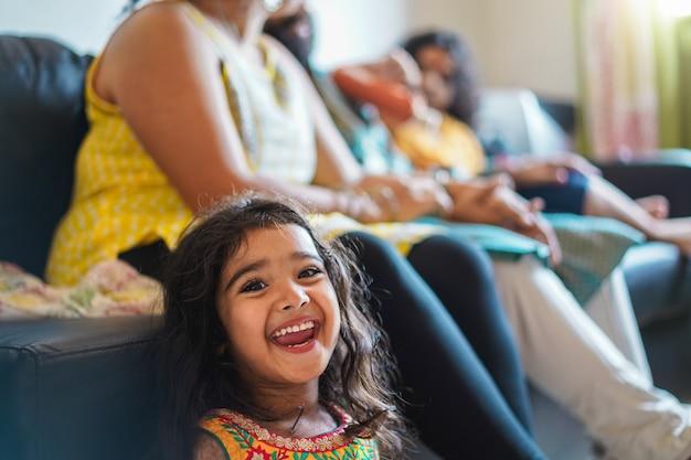 Felice ragazza indiana bambino che indossa un abito sari seduto sul divano con i genitori a casa