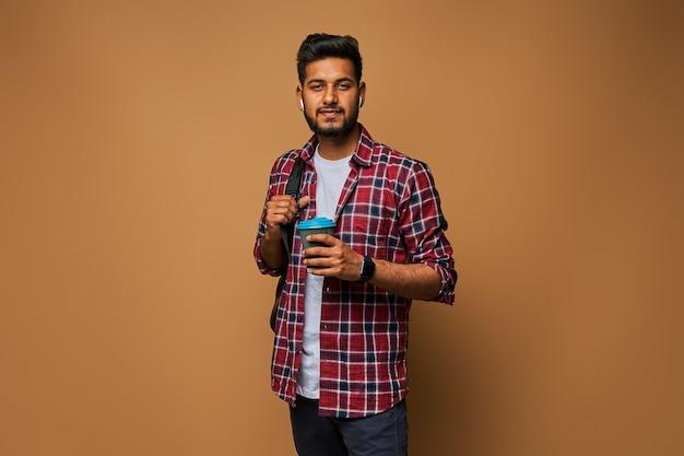 Felice uomo indiano in abiti casual con caffè per andare e zaino sulla parete pastello