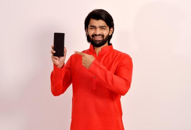 Uomo indiano felice che indica allo schermo del telefono cellulare vuoto per pubblicità, app utile o sito web.