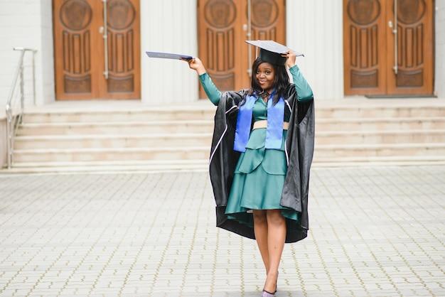 Felice studente universitario indiano in abito da laurea e berretto con certificato di diploma. ritratto di razza mista asiatica indiana e africana.