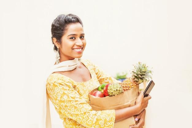 Felice donna indiana in abito etnico con in mano un pacchetto di frutta e un telefono