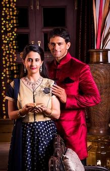 Felice coppia giovane indiana a namaskara o posa con le mani giunte al festival di diwali, accogliendo gli ospiti
