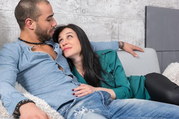 Felice coppia internazionale di uomo con la barba e sua moglie bruna seduta in un abbraccio sul divano del soggiorno
