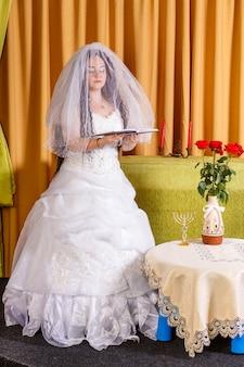 Sposa ebrea felice in un vestito bianco lussureggiante, viso velato che prega per la felicità nel matrimonio prima della cerimonia hupa. foto verticale