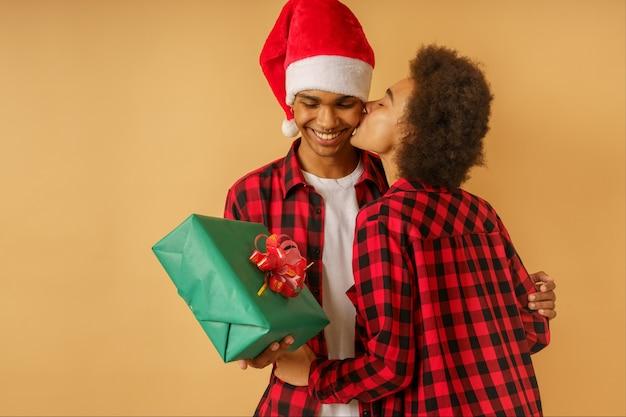 Felice e gioiosa coppia afro si scambia il regalo di natale