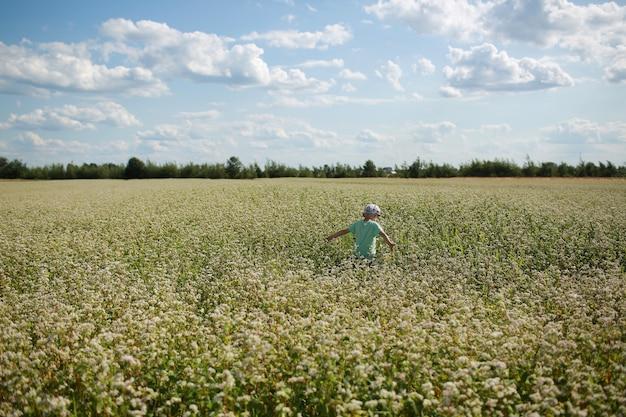 Il ragazzo allegro felice sta giocando sul prato fiorito. bambino divertirsi in campo all'aperto. estate, vacanza, concetto di infanzia.