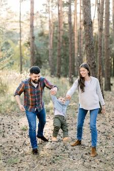 Felice famiglia gioiosa, bel padre barbuto, madre bella mora e adorabile figlio bambino carino, tenendosi per mano e camminando nella pineta autunnale con alberi di pino