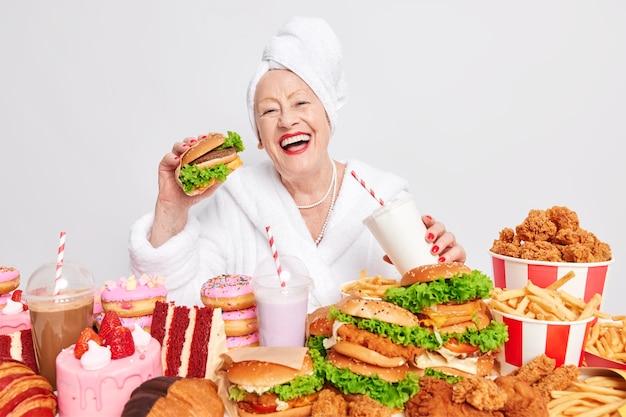 La donna rugosa anziana felice e allegra mangia hamburger deliziosi beve soda consuma fast food malsano