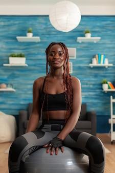 Felice gioiosa donna africana sorridente che si rilassa sulla palla svizzera, dopo un intenso allenamento sportivo duro sul tappetino da yoga nel soggiorno di casa. allegro forte atletico in forma africana utilizzando la palla di stabilità.