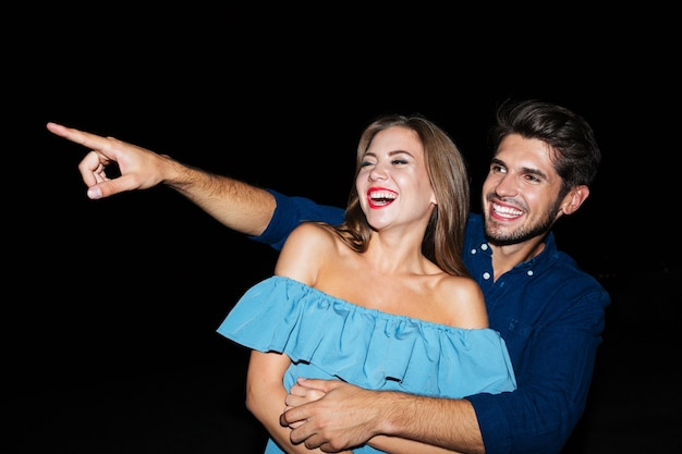 Felice gioiosa giovane coppia che ride e indica via di notte