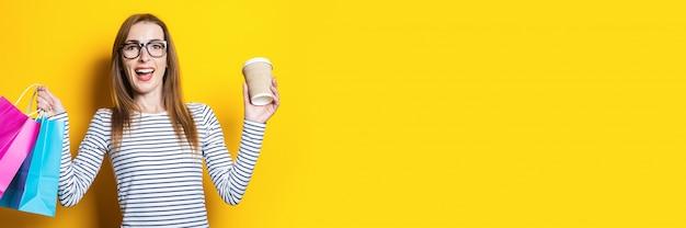 Ragazza giovane gioiosa felice con un bicchiere di carta e con le borse della spesa su uno sfondo giallo
