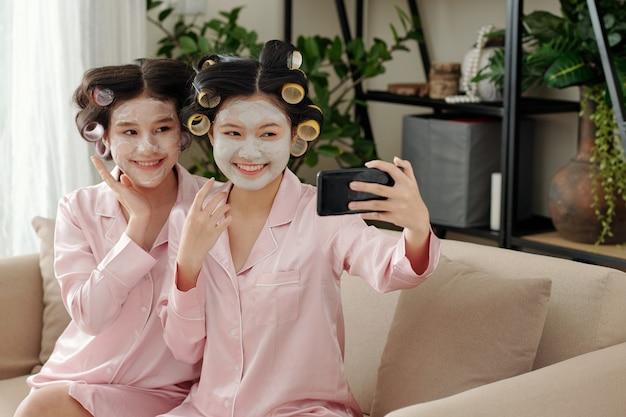 Felice gioiosa giovani donne vietnamite che prendono selfie dopo aver applicato la maschera di argilla sui volti per idratare...