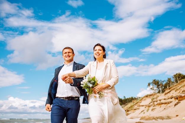 Felice coppia di mezza età appena sposata cammina in spiaggia e si diverte il giorno d'estate.