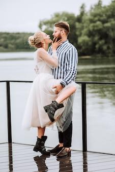 I felici appena sposati ridono, si divertono e gioiscono sulla banchina.