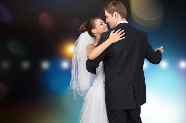 Felice coppia appena sposata che balla su sfondo sfocato