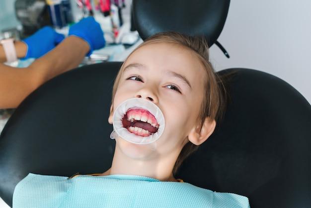 Bambino felice in clinica che fa cure odontoiatriche aiuto per la professione di trattamento dei denti dei bambini