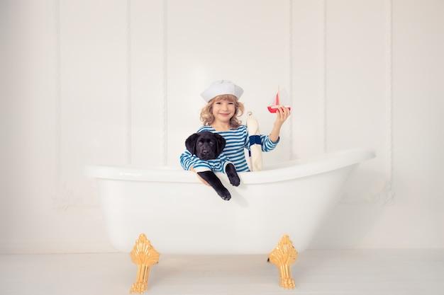 Bambino felice vestito da marinaio. bambino che gioca con il cane a casa. concetto di viaggio e avventura