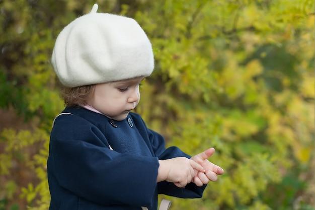 Il bambino felice gode del clima autunnale. piccola ragazza in foglie di autunno.