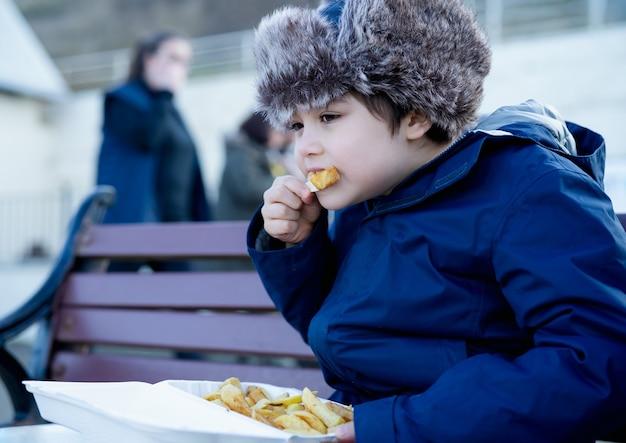 Bambino felice che gode di mangiare patatine fritte per pranzo, primo piano viso ragazzo carino che mangia patatine fritte.