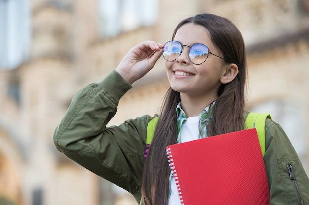 Ragazzo felice aggiusta gli occhiali per vedere meglio tenendo il libro scolastico autunno all'aperto, vista.