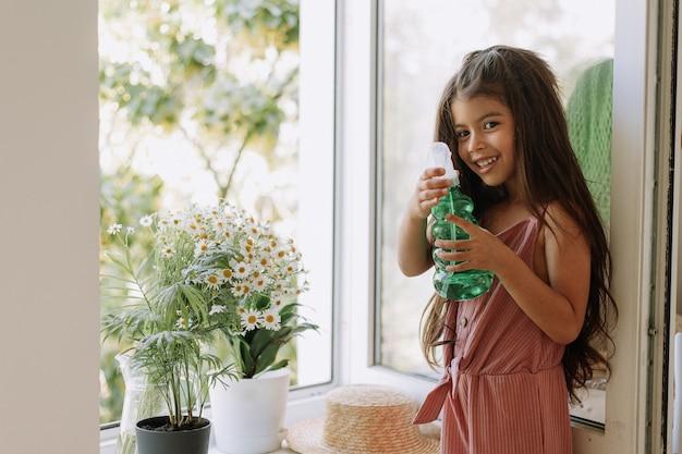 Una bambina felice che si prende cura delle piante d'appartamento a casa vestita con un elegante abito rosa polveroso