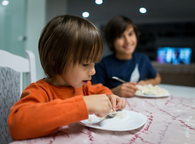 Bambino felice a casa a mangiare cibo