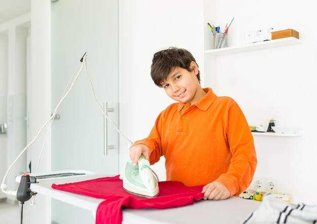 Bambino felice a casa stirare i vestiti
