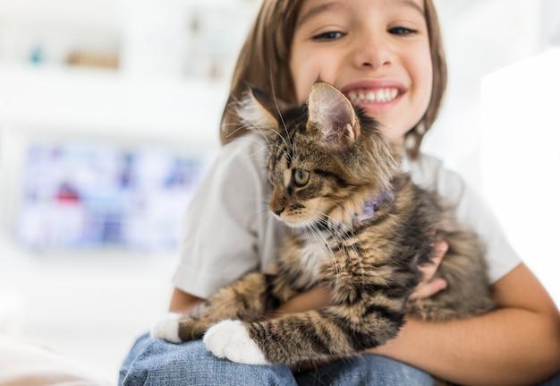 Bambino felice a casa giocando con gattino gatto