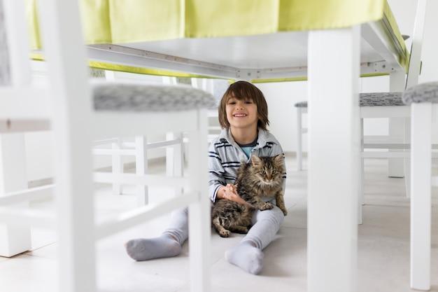 Bambino felice a casa con gatto domestico