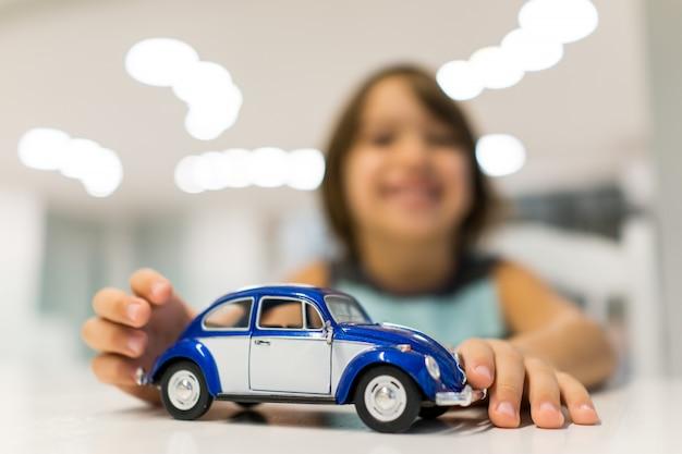 Bambino felice a casa con il gioco del giocattolo dell'automobile del oldtimer