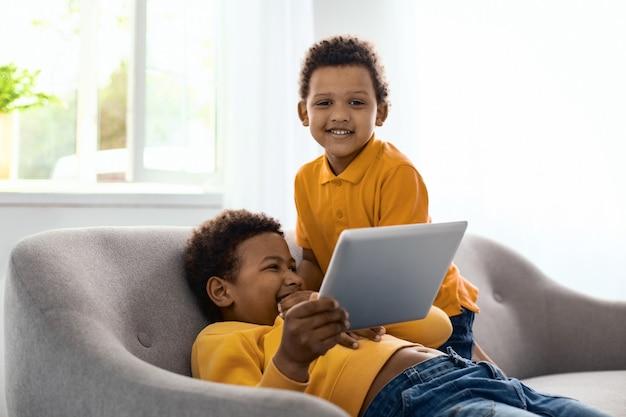 Ragazzo felice. ragazzino gioioso in posa per la fotocamera e sorridente mentre guarda un cartone animato con suo fratello su tablet e solleticandolo