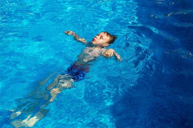Bambino felice che gioca nell'acqua blu della piscina in un resort tropicale al mare.