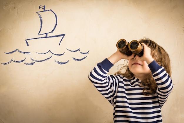 Bambino felice che gioca al coperto bambino guarda disegno di viaggio in nave e concetto di avventura vacanze estive