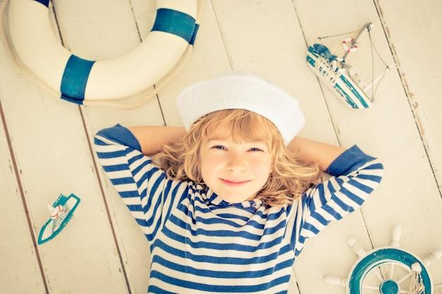 Bambino felice che gioca con la barca a vela giocattolo a casa. concetto di viaggio e avventura