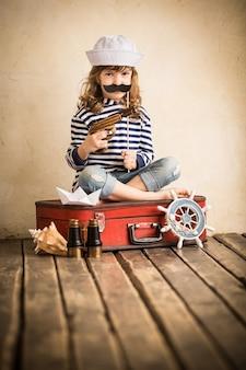 Bambino felice che gioca con la barca a vela giocattolo al chiuso. concetto di viaggio e avventura