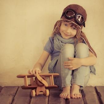 Bambino felice che gioca con un aeroplano di legno giocattolo al chiuso