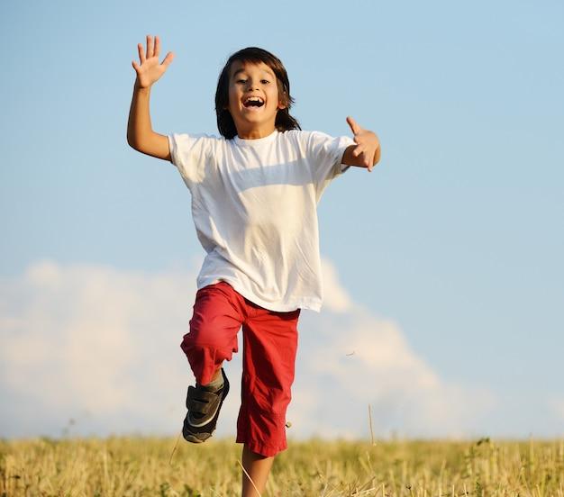 Bambino felice che corre sul bellissimo campo
