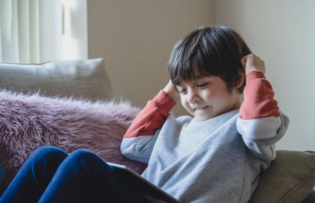 Felice bambino seduto sul divano havig divertimento prendendo con i suoi amici di classe su tablet, bambino che studia online su tavoletta digitale